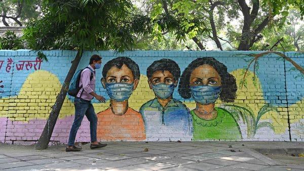 A man walks past in front of a mural depicting Covid-19 coronavirus awareness, in New Delhi.