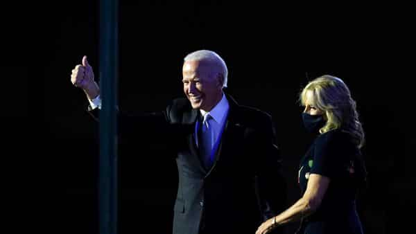 US President-elect Joe Biden stands on stage with his wife Jill Biden as he gives the thumbs-up to the cheering crowd beyond the protective glass. (AP)