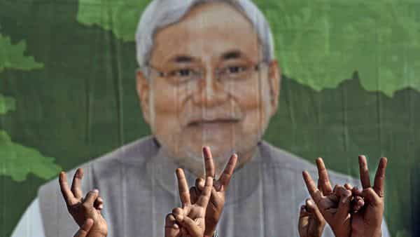 A poster of Bihar CM Nitish Kumar seen with the victory signs of JDU supporters. (ANI)