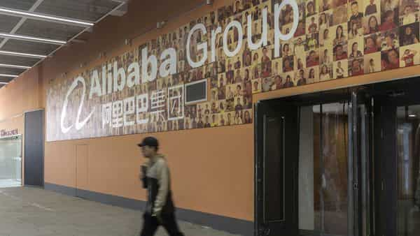 An employee walks near a photo wall at Alibaba Group Holding Ltd's headquarters in Hangzhou, China,. (Bloomberg)
