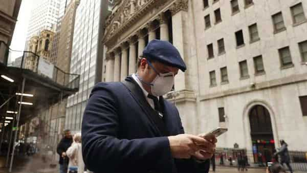FILE PHOTO: A man wears a protective mask as he walks past the New York Stock Exchange  (REUTERS)