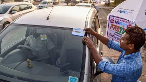 A worker fixes a FASTag sticker on the windscreen of a car. (Photo: PTI)