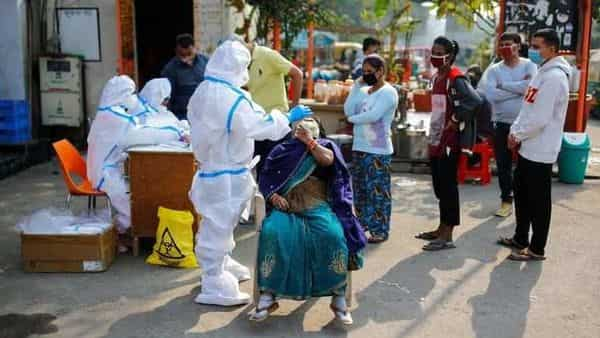 A healthcare worker wearing personal protective equipment (PPE) collects a swab sample from a woman amidst the spread of the coronavirus disease (COVID-19), at Delhi-Uttar Pradesh border, in Noida.  (REUTERS)