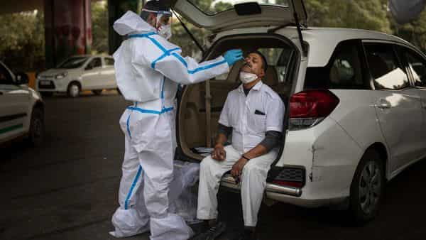 A health worker takes a nasal swab sample of a man to test for COVID-19 (AP)