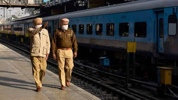 Punjab Police personnel walk along a platform at a railway station in Amritsar on as train services prepare to resume after farmers unions announced the suspension of blockades  (AFP)