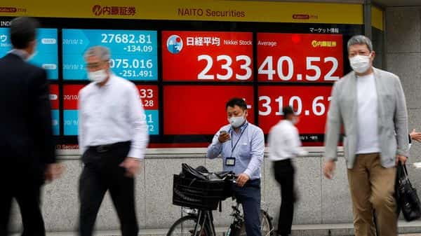 FILE PHOTO: Passersby wearing protective face masks walk past a screen displaying Nikkei share average and world stock indexes outside a brokerage, amid the coronavirus disease (COVID-19) outbreak, in Tokyo,  (REUTERS)