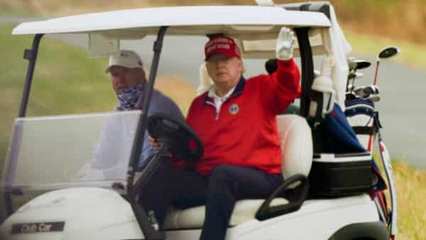 US President Donald Trump waves from a golf cart as he plays golf at Trump National Golf Club. (AP)