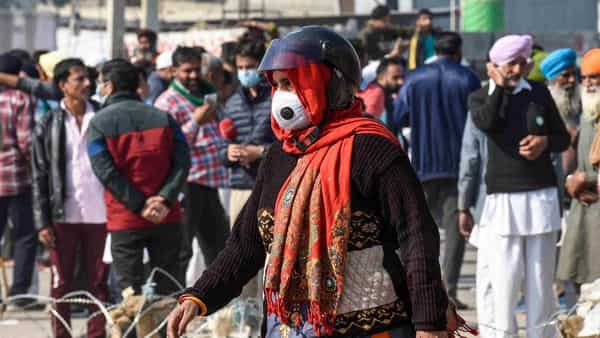 New Delhi: A woman, wearing a helmet, attempts to cross Singhu border on foot, during the ongoing farmers 'Delhi Chalo' protest march  (PTI)
