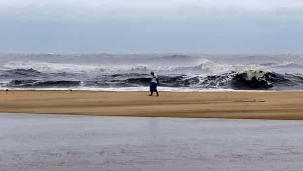 A man walks past strong waves at Marina Beach in Chennai, India. (AP)
