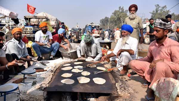 Farmers make chapatis during a protest against the new farm laws, at the Singhu Border in New Delhi on Wednesday. (ANI Photo)