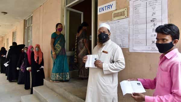 Voters show their Voter ID slips as they stand in a queue to vote for the GHMC election, in Hyderabad on Thursday (ANI Photo )