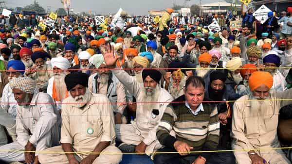 Farmers sitting at Singhu Border during their protest against the new farm laws, in New Delhi on Friday (ANI)