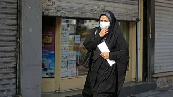 A woman wearing a face mask amid the covid-19 pandemic walks by closed shops in the Iranian capital Tehran (AFP)