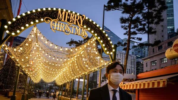 In a photo taken on December 2, 2020 a man wearing a face mask walks along a street beneath Christmas decorations in central Seoul. (Photo by Ed JONES / AFP) (AFP)