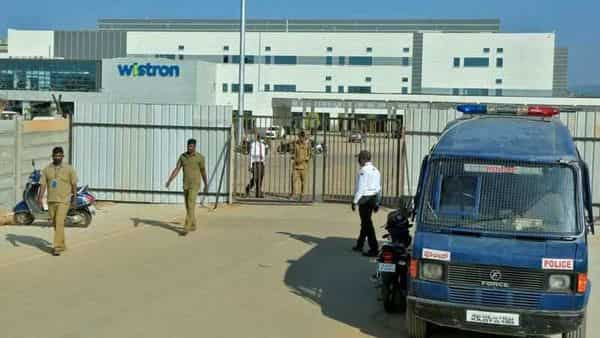Policemen stand guard outside a facility run by Wistron Corp near Bengaluru (REUTERS)