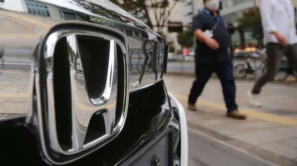 People walk by a Honda car displayed in front of a Honda Motor Co. showroom in Tokyo, Monday, Nov. 2, 2020. Japanese automaker Honda reported Friday, Nov. 6, 2020 that its profit rose 23% from a year earlier in the last quarter, despite a pandemic that has slammed businesses around the world. (AP Photo/Koji Sasahara) (AP)