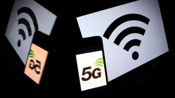 The 5 G wireless technology logo is displayed on a smartphone and a wireless signal sign displayed by a tablet (AFP)