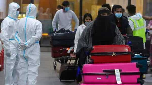 Passengers arriving from United Kingdom walk past Indian municipal workers in personal protective equipment (PPE) at Chhatrapati Shivaji Maharaj International Airport in Mumbai, India, Tuesday, Dec. 22, 2020. Dozens of countries around the world slapped tough travel restrictions on the U.K. because of a new and seemingly more contagious strain of the coronavirus in England. From Canada to India, one nation after another banned flights from Britain. (AP Photo/Rafiq Maqbool) (AP)