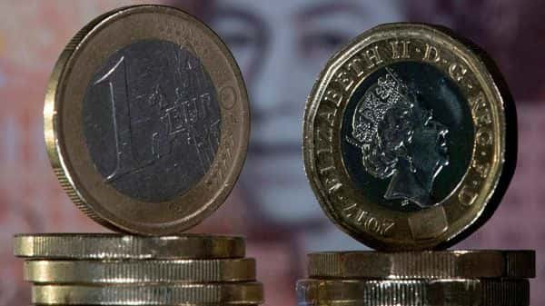 A British one pound sterling coins and one Euro coins in front of a British ten pound sterling note (AFP)