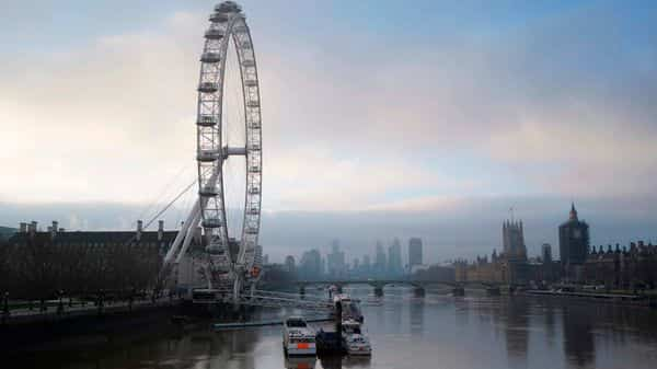 The London Eye attraction (L) and Britain's Houses of Parliament (R) are seen on the banks of the River Thames at sunrise in London on December 31, 2020 on the day that the Brexit transition period ends and Britain leaves the EU single market and customs union four-and-a-half years after voting to leave the bloc. (AFP)