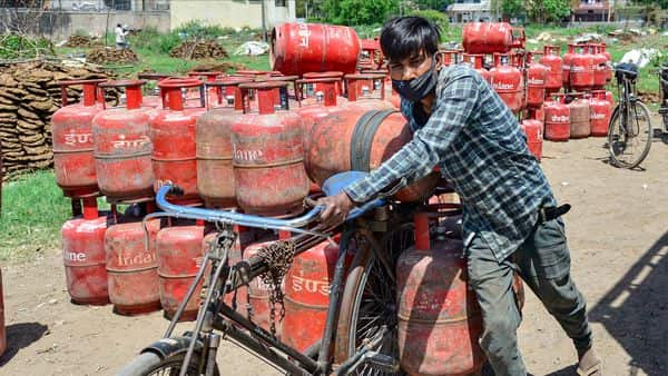 A worker carries LPG gas cylinders on his bicycle for delivery during the nationwide lockdown imposed in the wake of coronavirus pandemic in New Delhi. (PTI)