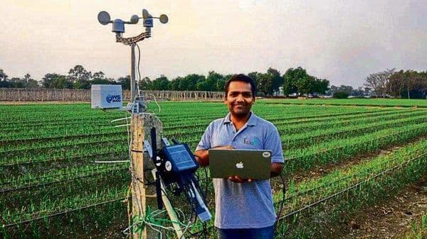 Fasal co-founder Ananda Verma with the startup's IoT device on a farm in Chhattisgarh.