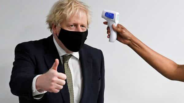 Britain's Prime Minister Boris Johnson gives a thumbs-up as he has his temperature checked during a visit to Chase Farm Hospital in north London, Britain. (REUTERS)