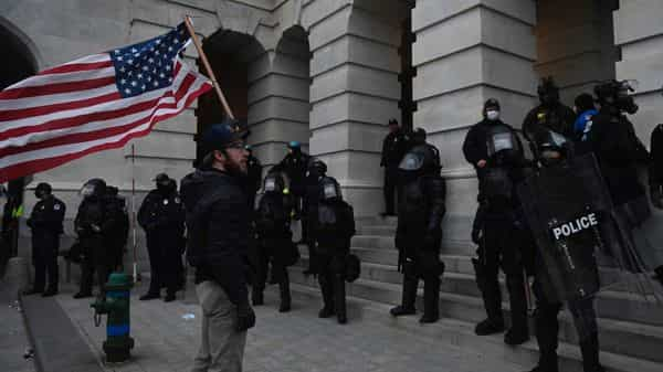 A Trump supporter confronts police and security forces at the US Capitol in Washington, DC. (AFP)