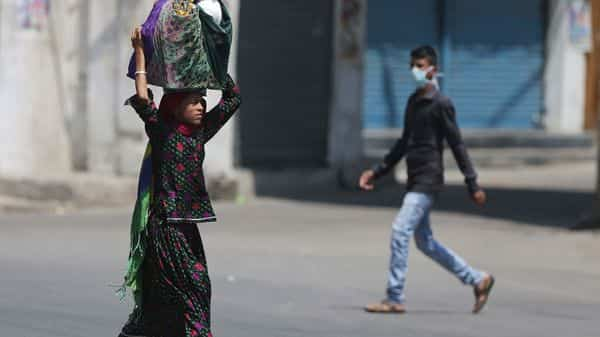 Indians walk on a deserted street in Hyderabad, India, Friday, March 27, 2020. Some of India's legions of poor and others suddenly thrown out of work by a nationwide stay-at-home order began receiving aid on Thursday, as both public and private groups worked to blunt the impact of efforts to curb the coronavirus pandemic. The measures that went into effect Wednesday, the largest of their kind in the world, risk heaping further hardship on the quarter of the population who live below the poverty line and the 1.8 million who are homeless. (AP Photo/Mahesh Kumar A.) (AP)