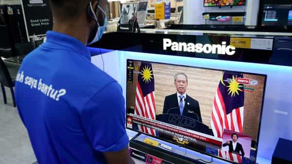 An electronic shop worker wearing a face mask watches a live broadcast of Malaysian Prime Minister Muhyiddin Yassin at a shopping outlet in Kuala Lumpur, Malaysia, Tuesday, Jan. 12, 2021. Malaysia's king Tuesday approved a coronavirus emergency that will prorogue parliament and halt any bids to seek a general election in a political reprieve for embattled Muhyiddin. (AP Photo/Vincent Thian) (AP)