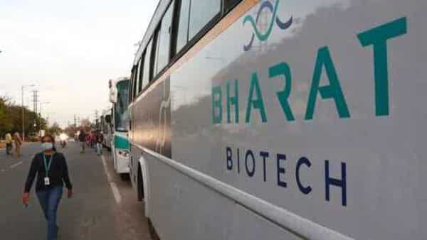 An employee of Bharat Biotech walks to board a bus parked outside the office on the outskirts of Hyderabad. (AP)