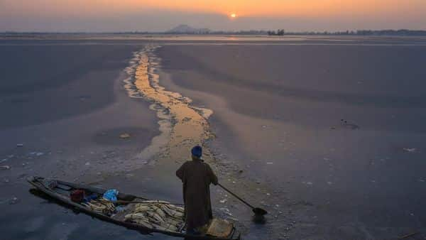 Srinagar: A vegetable vendor row his boat after breaking the frozen surface of Dal Lake, during sunset in Srinagar, Tuesday.  (PTI)