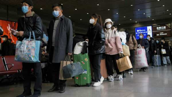 FILE PHOTO: Travellers wearing face masks line up to board a train at a railway station following the outbreak of the coronavirus disease (COVID-19) in Beijing, China, January 13, 2021. REUTERS/Thomas Peter/File Photo (REUTERS)