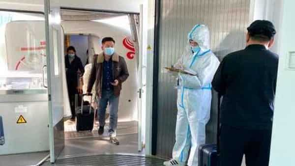 Passengers wearing face masks to protect against the spread of coronavirus exit a plane after arriving at Wuhan Tianhe International Airport in Wuhan. (AP)