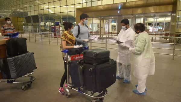 Airport staff in protective suits check passengers at Mumbai Airport. (PTI)