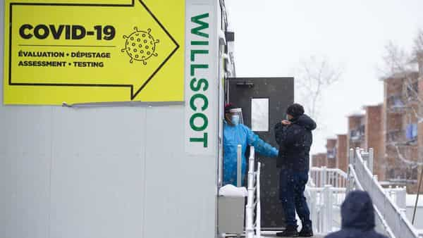 A healthcare worker in protective gear speaks with a person standing in line to enter a Covid-19 testing site in Montreal, Quebec, Canada (Bloomberg)