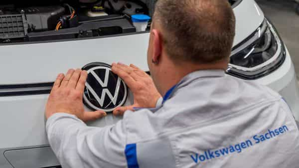 FILE PHOTO: An employee fixes a VW sign at the company's production line  (REUTERS)