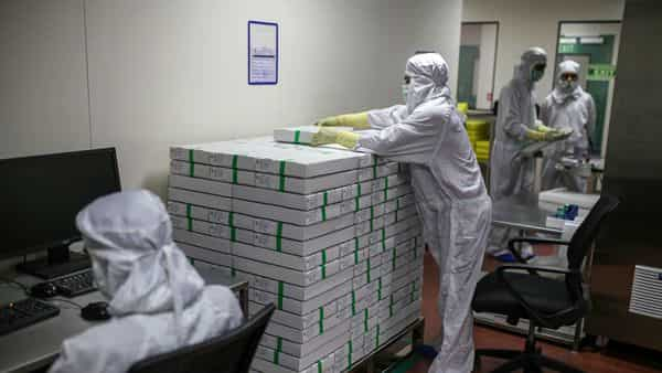 A employee stacks packed vials of Covishield, the local name for the Covid-19 vaccine developed by AstraZeneca Plc. and the University of Oxford, on the production line at the Serum Institute of India Ltd. Hadaspar plant in Pune. (Bloomberg)
