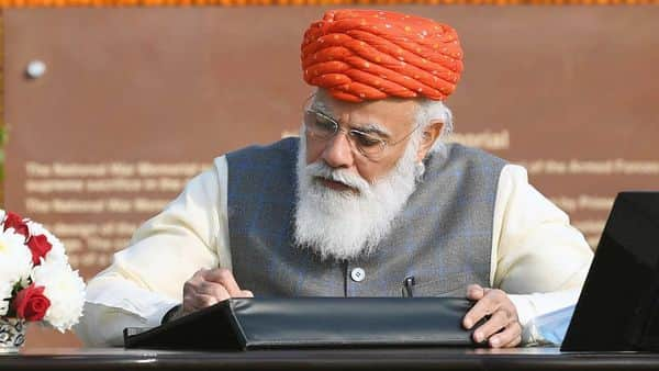 Prime Minister Narendra Modi signing the visitor's book at the National War Memorial, on the occasion of the 72nd Republic Day. (ANI)