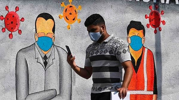 A pedestrian walks past a wall mural painted to thank frontline workers from various professions fighting against the spread of Covid-19 in Mumbai. (AFP)