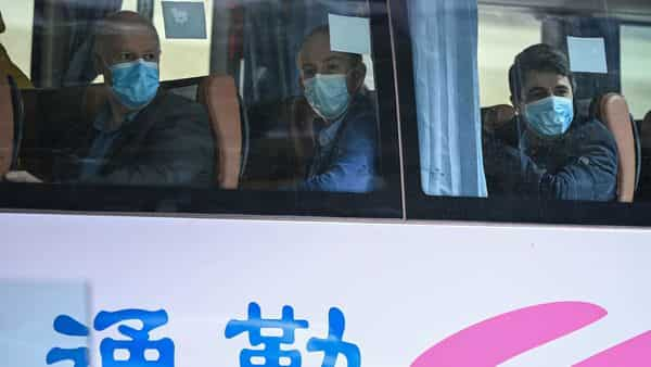 Members of the WHO team investigating the origins of the Covid-19 coronavirus leave The Jade Hotel on a bus after completing their quarantine in Wuhan, China (Photo: AFP)