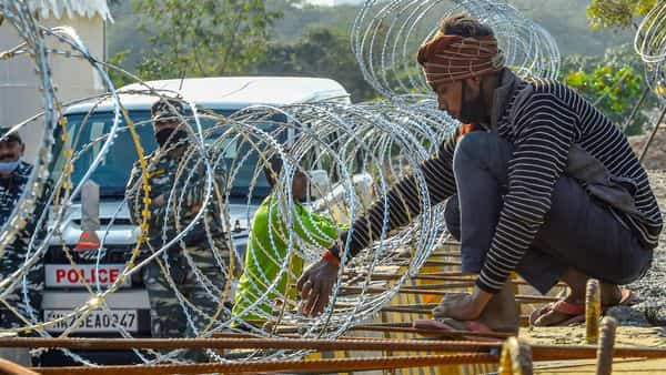 Workers use barbed wires to construct a barricade at Singhu Border during the ongoing farmers' agitation in New Delhi. (PTI)