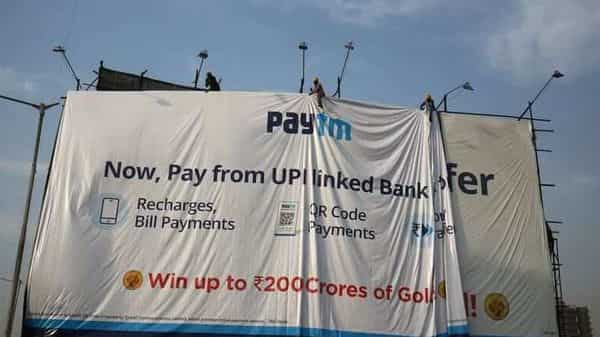 FILE PHOTO: Workers adjust a hoarding of Paytm, a digital payments firm, in Ahmedabad, India.  (REUTERS)