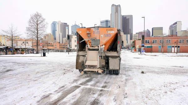 A City of Dallas Mobility and Street Services truck spreads de-icing materials on a road in downtown Dallas (AP)