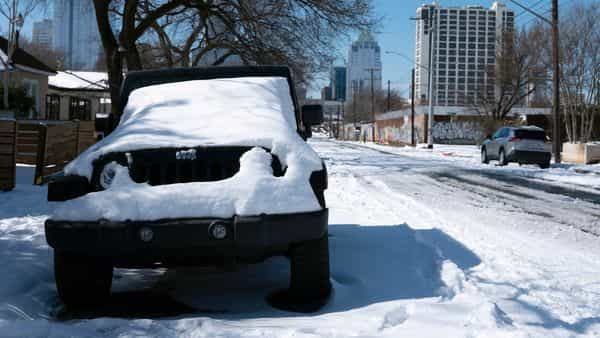A parked Jeep is covered in snow on Tuesday (AP)