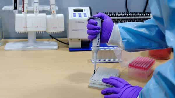 A healthcare worker uses a pipette to process Covid-19 test samples.