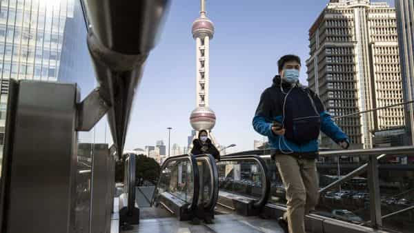 Pedestrians wearing protective masks ride on an escalator in Pudong's Lujiazui Financial District in Shanghai, China (Bloomberg)