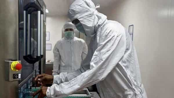 An employee in PPE removes vials of AstraZeneca's COVISHIELD, coronavirus vaccine from a visual inspection machine inside a lab at Serum Institute of India, Pune. (REUTERS)