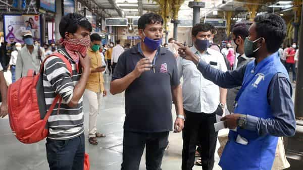 A BMC official collects fine from commuters for not wearing face masks at CSMT in Mumbai. (PTI)