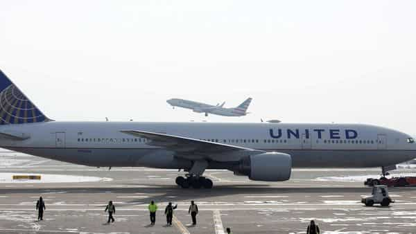 A United Airlines Boeing 777-200ER plane is towed as an American Airlines Boeing 737 plane departs from O'Hare International Airport in Chicago, Illinois. (REUTERS)